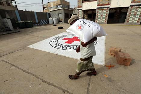 Mies kantoi Kansainvälisen Punaisen ristin avustussäkkiä Hodeidahin satamassa Jemenissä kesäkuussa 2018.