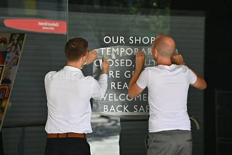 John Lewis -tavaratalon työntekijät asettelevat kylttiä näyteikkunaan Lontoon Oxford Streetillä 16. kesäkuuta. Edellisenä päivänä Englannin koronarajoitukset höllenivät ja moni kauppa avasi ovensa liki kolmen kuukauden kiinniolon jälkeen.