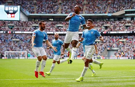 Manchester Cityn Raheem Sterling (kesk.) juhli joukkuetovereidensa kanssa ottelun johtomaalia sunnuntaina.