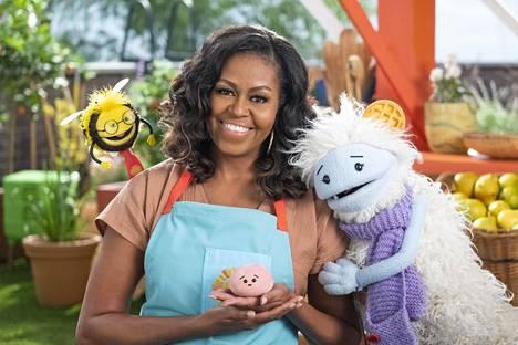Sarjan tuottajalla Michelle Obamalla on vastanäyttelijöinään nukkehahmot Kimi (vas.), Mochi ja Vohvis.
