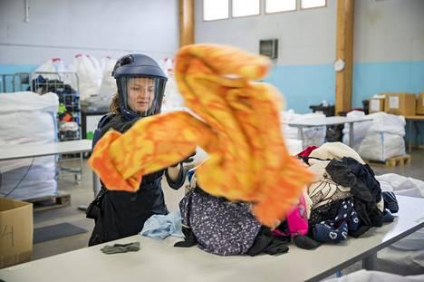 Lajittelija Sallamari Salmi erottelee vaatteet valmistusmateriaalin mukaan poistotekstiilin lajittelukeskuksessa.