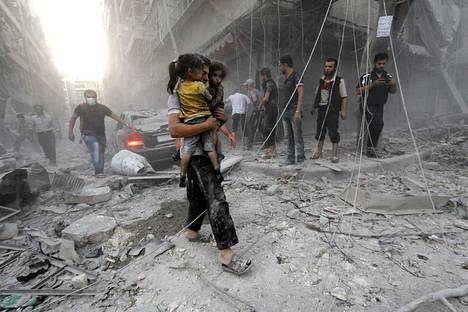 Syyrialainen mies kantoi pölyn peittämiä tyttöjä turvaan maan hallituksen joukkojen tekemän ilma-iskun jälkeen Aleppossa.
