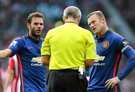 Juan Mata (vas.) ja Wayne Rooney käyvät tiukkaa keskustelua erotuomari Martin Atkinsonin kanssa.