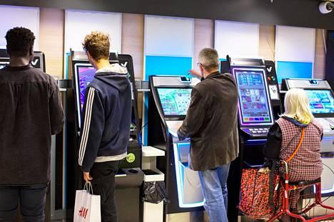 Monessa maassa rahapelikoneita on lähinnä pelisaleissa, mutta Suomessa pelikoneet on hajasijoitettu. Pelaajia ruokakaupassa Helsingissä elokuussa.