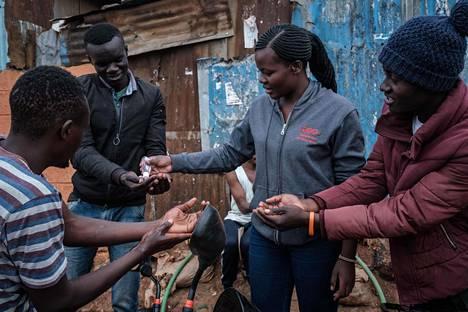 Vapaaehtoistyöntekijä jakaa käsidesiä ihmisille Kiberan slummialueella Nairobissa Keniassa.