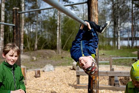 Otso Lummaa, Bruno Lehtiniemi ja Eemeli Rajala leikkivät kiipeilytelineellä, joka on osa koulun parkour-rataa.