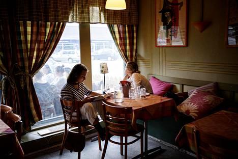 (19.05) Monipäiväiset elokuvajuhlat ovat hyvin sosiaalinen tapahtuma. Ystävien kanssa nukutaan vieri vieressä, katsotaan lukuisia elokuvia ja jutellaan päivästä toiseen. Helmi Kanerva Päällysaho (vas.) ja Viena Auvinen vetäytyivät kolmantena festivaalipäivänään Päivin kammari -ravintolan rauhaan, Päällysaho lukemaan kirjaa ja Auvinen kirjoittamaan päiväkirjaa.