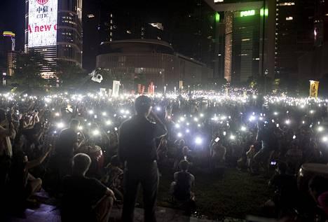Demokratia-aktivistit heiluttivat sunnuntaina matkapuhelimiaan ja taulutietokoneitaan Hongkongin hallintokeskuksen edustalla järjestetyssä mielenosoituksessa.
