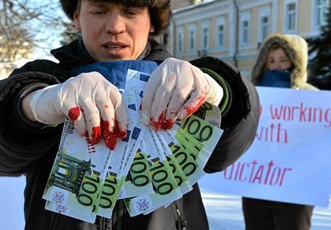 Mielenosoittajat vaativat että Deutsche Bank lopettaisi yhteistyön presidentti Viktor Janukovytšin omistamien pankkien ja yritysten kanssa.
