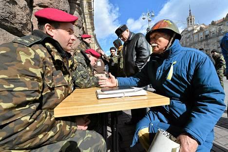 Itsepuolustusjoukkojen vanhempi aktivisti keskustelee värväyspisteellä ukrainalaisupseerin kanssa Kiovassa tiistaina.