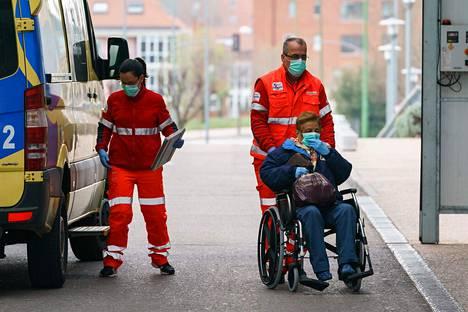 Ensihoitajat kuljettivat iäkästä naispotilasta pyörätuolilla sairaalaan pohjoisespanjalaisessa Burgosissa lauantaina.