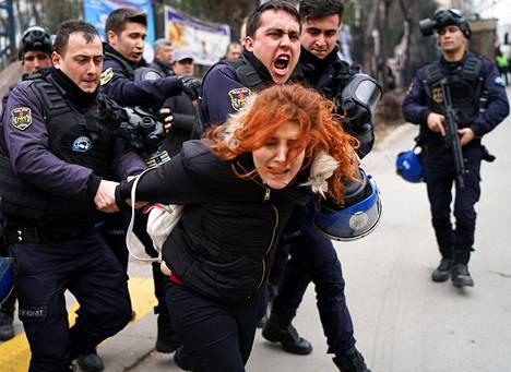 Poliisi retuuttaa mielenosoittajaa Turkin pääkaupungissa Ankarassa perjantaina. Cebecin yliopistokampuksella protestoitiin vallankaappausyrityksen jälkeen tehtyjä opettajien potkuja vastaan.