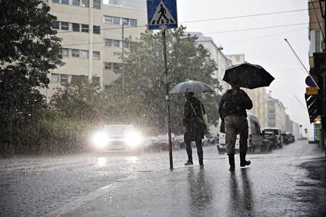 Ihmisiä sateessa Hakaniemessä.