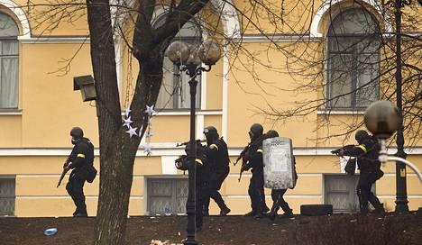 Aseistautuneet poliisit etsimässä tuliasemaa Itsenäisyyden aukiolla Kiovassa 20. päivä helmikuuta.