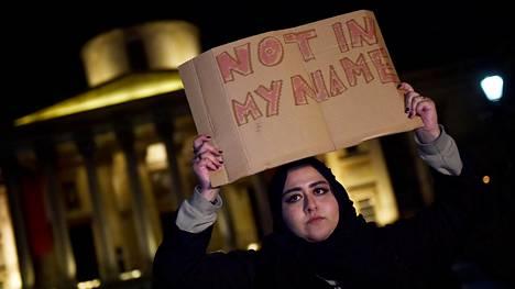 """Lontoolaisnainen osallistui terrori-iskujen muistotilaisuuteen Trafalgar Square -aukiolla torstaina. Kyltissä lukee """"Ei minun nimissäni""""."""