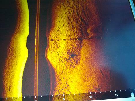 Esimerkkikuva viistokaikuluotaimen tuottamasta kuvasta. Kuva ei liity kadonneen nuoren miehen tapaukseen. Kuvassa on pohjaan painotettu vesijohto kivikkoisella pohjalla.