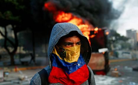Hallituksenvastainen mielenosoittaja käveli palavan kioskin ohitse Venezuelan pääkaupungissa Caracasissa sunnuntaina.