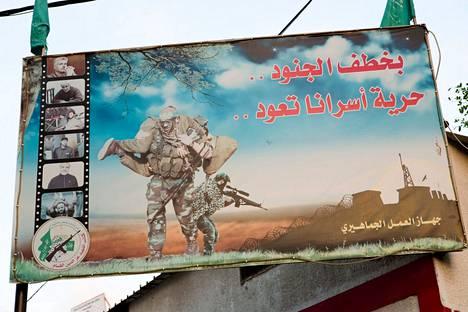 Hamasin militanttisiipi Al-Qassamin ulkomainosjuliste, jossa Hamasin militantti kantaa panttivangiksi ottamaansa Israelin sotilasta.
