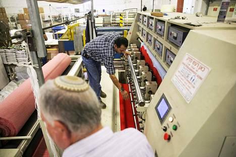 Työntekijöitä tekstiilitehtaassa Länsirannan juutalaissiirtokunta-alueella sijaitsevalla Barkanin teollisuusalueella. Kuva vuodelta 2015.