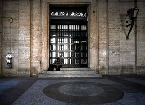 Italia on kärsinyt merkittävästi koronaepidemiasta ja joutunut tekemään tiukkoja rajoitustoimia. Koditon mies istui suljetun kauppakeskuksen edessä Roomassa.