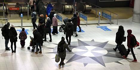 Matkustajia Rautatientorin metroasemalla Helsingissä joulukuussa.