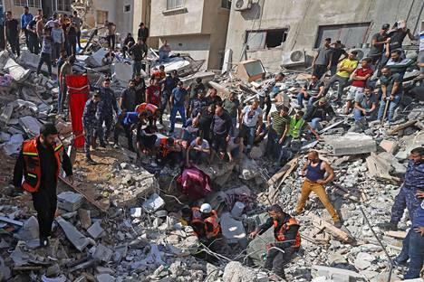 Lääkintätyöntekijät etsivät eloonjääneitä Israelin pommittaman talon raunioista Gazassa sunnuntaina.
