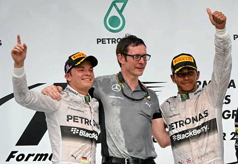 Mercedeksen Nico Rosberg (vas.) ja Lewis Hamilton (oik.) juhlivat Malesian kisan menestystä palkintopallilla mukanaan tallin pääinsinööri Andy Shovlin.