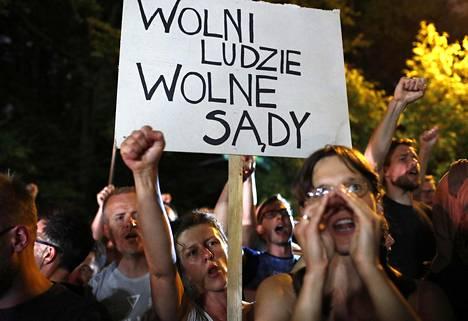Mielenosoittajat kokoontuivat parlamentin ulkopuolelle Varsovassa perjantaina.