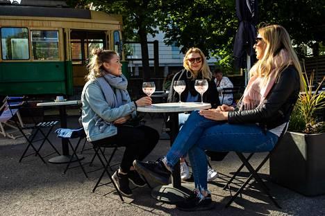 Emilia Eräste, Miia Hämäläinen ja Senni Niemi nauttivat juomia yhdellä Teurastamon terasseista.