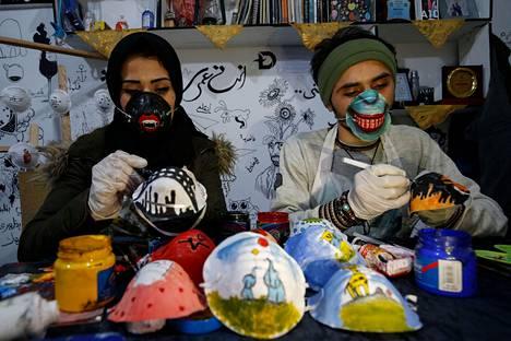 Palestiinalaistaitelijat Samah Said (vas.) ja Dorgham Krakeh maalaavat hengityssuojaimia Gazassa.