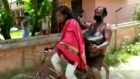 Videon pysäytyskuva Jyoti Kumarista pyöräilemässä isänsä kanssa kotikyläänsä.