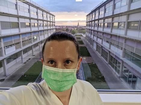 Infektiolääkäri Sari Arponen taustallaan sairaalan sisäpiha. Horisontissa näkyy Madridin Vallecasin kaupunginosa, jonka asukkaita kyseinen sairaala palvelee.