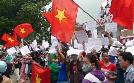 Vietnamilaiset mielenosoittajat heiluttivat keskiviikkona lippuja ja kylttejä tehtaan edustalla Binh Duongin maakunnassa.