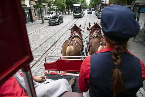 Jyllanninhevoset Gunnar ja Frederik kulkevat tottuneesti raitiovaunujen ja muun liikenteen seassa.