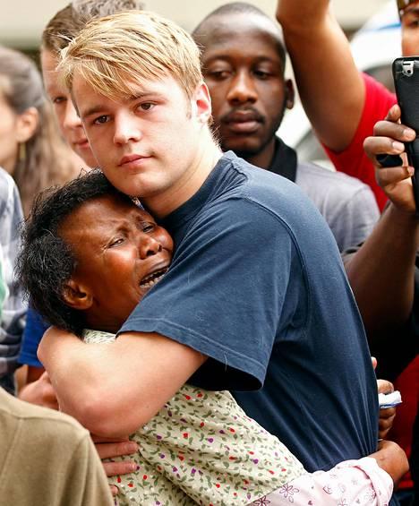 Eteläafrikkalaiset lohduttivat toisiaan Nelson Mandelan kotitalon edessä Johannesburgissa perjantaina.