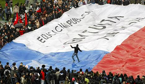 Mielenosoittaja käveli valtavan Chilen lipun päällä opiskelijoiden suurmielenosoituksessa Santiagossa. Lipussa vaaditaan laadukasta ja ilmaista opetusta.