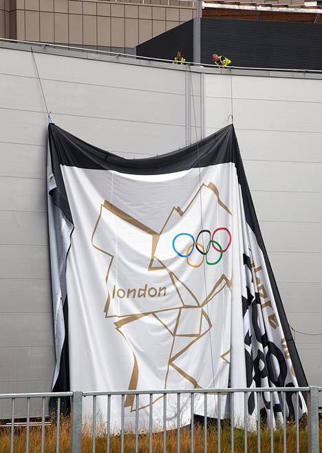Jättiläismäinen olympialakana pudotettiin maanantaina kisapuistoa koristavasta seinästä.