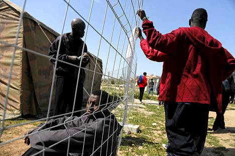 Afrikasta paenneet siirtolaiset nojailivat aitaan pakolaiskeskuksessa Melillassa 19. maaliskuuta.