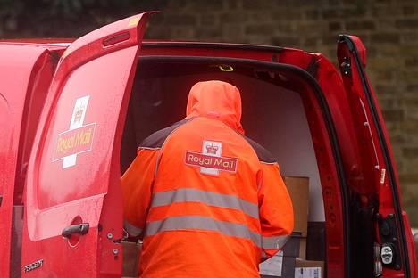 Royal Mail -postiyhtiön työntekijä jakamassa postia Lontoossa tammikuussa. Koronapandemia on hidastanut jakelua joillakin alueilla.