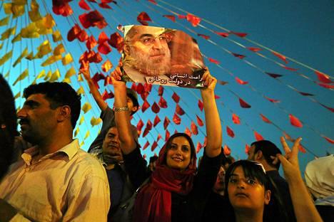 Iranilaisen juhlivat uutta presidenttiä Hasan Ruhania (julisteen kuvassa).