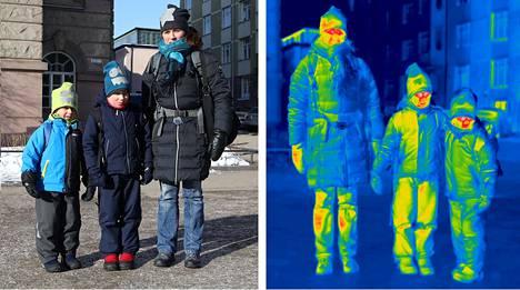 """Jyväskyläläiset Heidi Nevalainen sekä lapset Juuso, 8, ja Joonas, 5, saapuivat tiistaina junalla hiihtolomalle Helsinkiin. Toppavaatteiden alle lomalaiset ovat pukeneet fleece-kerrastoja. Varrelliset toppakengät lämmittävät etenkin kun alla on vielä villasukat. """"Jyväskylästä lähtiessä ajattelin vielä, että ei täällä nyt niin kylmä ole. Onneksi on kerrastoja. Helsingissä tuuli tekee pakkasesta kylmemmän"""", Heidi Nevalainen kertoo. Oikeanpuoleisessa lämpökameralla otetussa kuvassa lapset ovat siirtyneet äidin vasemmalle puolelle."""