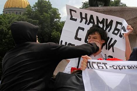 Huppupäinen mies hyökkäsi homojen oikeuksia puolustavien mielenosoittajien kimppuun Pietarissa viime kesäkuussa.