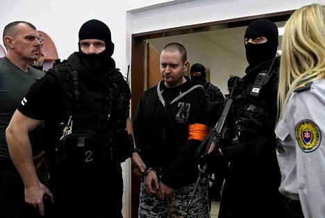 Miroslav Marček tuotiin oikeuteen tiukassa poliisivartiossa kun murhaoikeudenkäynnit alkoivat joulukuussa 2019.