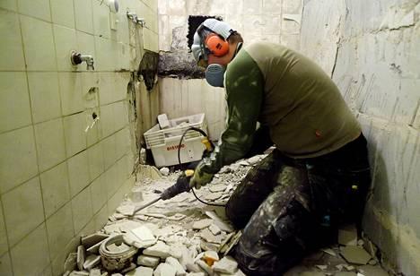 Rakentaja irrottaa vanhoja laattoja kylpyhuoneremonttikohteessa Helsingissä.