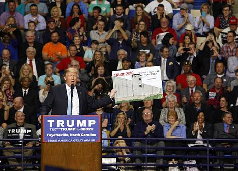 Donald Trump piteli muurihankettaan tukevaa kannattajansa piirrosta vaalitilaisuudessaan maaliskuussa 2016 Pohjois-Carolinan Fayettevillessa.