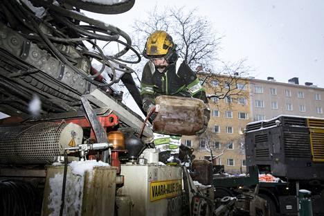 Poraaja Markku Martikainen Rototecista kaataa polttoöljyä porauskoneen tankkiin.