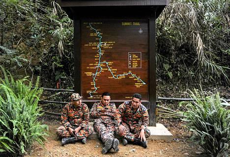 Maanjäristyksen jälkeen paikalle hälytetyt pelastustyöntekijät hetken levähdyksellä Malesian Kinabalu-vuorella lauantaina.