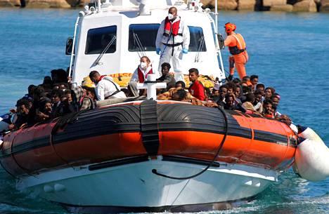 Pelastusalus toi mereltä pelastettuja ihmisiä rantaan Lampedusalla sunnuntaina.
