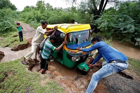 Ihmiset yrittivät työntää riksaa liikkeelle tulvan valtaamalla tiellä Ahmedabadin kaupungin lähellä Intiassa perjantaina.