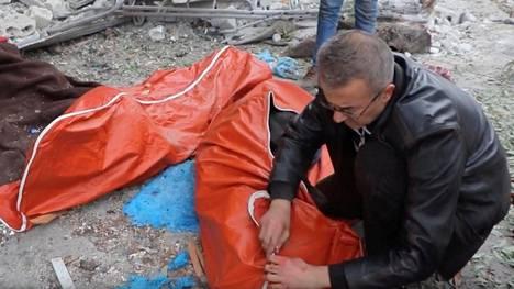 Itä-Aleppon kapinallisalueilla asuva mies peitti kadulle osuneessa tykistökeskityksessä kuolleiden ruumiita keskiviikkona.